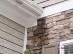 improper-roof-flashing-allows-water-run-down-front-of-manufactured-stone-veneer-wall